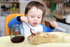 Il bambino mangia i pancake con inceppamento Fotografie Stock Libere da Diritti