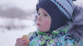Il bambino mangia l'inverno dei biscotti all'aperto archivi video