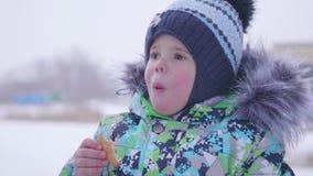 Il bambino mangia l'inverno dei biscotti all'aperto Passeggiata nell'aria fresca stock footage
