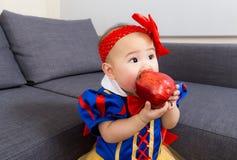 Il bambino mangia la mela con il condimento del partito di Halloween fotografia stock libera da diritti