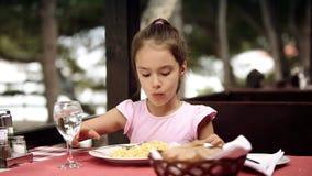 Il bambino mangia la pasta degli spaghetti nel ristorante che è situato sulla riva archivi video