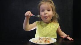 Il bambino mangia il riso ed i funghi cucinati con un cucchiaio su un fondo nero alla tavola nera archivi video
