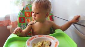 Il bambino mangia su un seggiolone stock footage