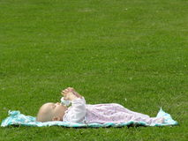 Il bambino mangia sull'erba Fotografia Stock
