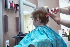 Il bambino maschio al negozio di barbiere, ha tagliato i capelli immagini stock