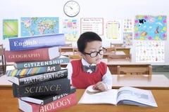 Il bambino maschio che studia con la lezione prenota nella classe Immagine Stock