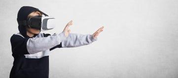 Il bambino maschio piccolo in vetri di realtà virtuale e della maglietta felpata gestures con le mani, le allunga in avanti, inte Immagine Stock Libera da Diritti
