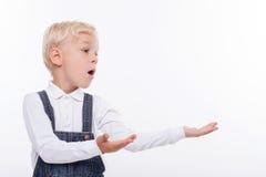Il bambino maschio sveglio sta presentando qualcosa con la gioia Fotografia Stock