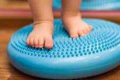 Il bambino massaggia i suoi piedi mentre sta sulla coperta Fotografia Stock