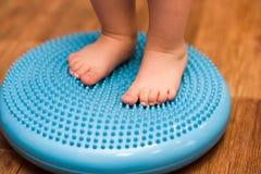 Il bambino massaggia i suoi piedi mentre sta sulla coperta Immagine Stock