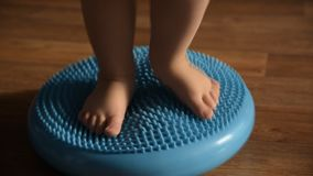 Il bambino massaggia i suoi piedi mentre sta sulla coperta stock footage