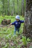 Il bambino 8-9 mesi impara camminare, passeggiate attraverso il legno che tiene un tronco di albero Bambina che sorride su una pa immagine stock