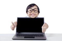 Il bambino mostra i pollici su con lo schermo vuoto del computer portatile Fotografia Stock