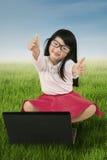 Il bambino mostra il segno GIUSTO con il computer portatile su erba Immagini Stock Libere da Diritti