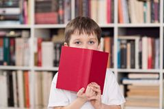 Il bambino nasconde il fronte dietro il libro i immagine stock libera da diritti