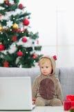 Il bambino nei cervi di natale costume lo sguardo in computer portatile Fotografia Stock Libera da Diritti