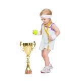 Il bambino nel tennis copre con la medaglia ed il calice Immagine Stock