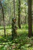 Il bambino nella foresta prende i funghi immagine stock