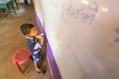Il bambino nella lezione alla scuola dai bambini cambogiani del progetto si preoccupa Immagine Stock