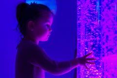 Il bambino nella stanza di stimolazione sensoriale di terapia, snoezelen Bambino che interagisce con la lampada colorata del tubo immagini stock libere da diritti