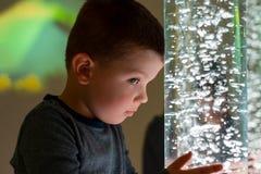 Il bambino nella stanza di stimolazione sensoriale di terapia, snoezelen Bambino che interagisce con la lampada colorata del tubo fotografia stock