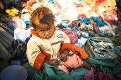 Il bambino non identificato sta sedendosi mentre i suoi genitori stanno lavorando allo scarico Fotografia Stock Libera da Diritti