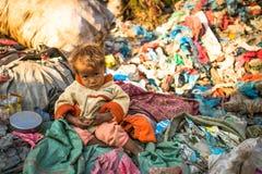 Il bambino non identificato sta sedendosi mentre i suoi genitori stanno lavorando allo scarico, il 22 dicembre 2013 a Kathmandu,  Fotografia Stock