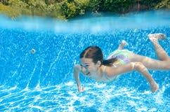 Il bambino nuota nell'adolescente che attivo subacqueo e felice della piscina la ragazza si tuffa e si diverte nell'ambito dell'a immagini stock