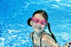 Il bambino nuota subacqueo nella piscina, adolescente che attivo felice la ragazza si tuffa e si diverte nell'ambito dell'acqua,  fotografia stock