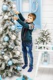 Il bambino orna l'albero di Natale Il ragazzo nel maglione con Fotografie Stock Libere da Diritti