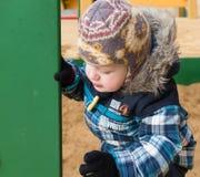 Il bambino ottiene da un lato della sabbiera ad un campo da giuoco e cerca la corrente alternata Immagini Stock Libere da Diritti