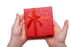 Il bambino passa giudicare un contenitore di regalo rosso isolato su un fondo bianco Vista superiore Immagine Stock