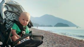 Il bambino in passeggiatore ha lasciato solo sulla spiaggia Piccolo bambino che si siede in carrozzina video d archivio