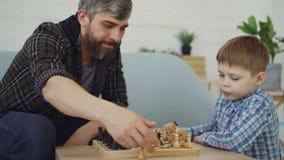 Il bambino piccolo abile sta giocando gli scacchi con i suoi chesspieces commoventi preoccupantesi del padre e pezzi degli scacch video d archivio