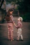 Il bambino piccolo e sua sorella vanno per la passeggiata Fotografie Stock Libere da Diritti
