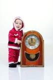 Il bambino piccolo nel vestito di Santa gioca con l'orologio d'annata in studio bianco Fotografie Stock