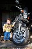 Il bambino piccolo sta vicino al grande motociclo immagine stock