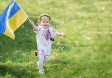 Il bambino porta l'ondeggiamento bandiera blu e gialla dell'Ucraina nel campo Festa dell'indipendenza del ` s dell'Ucraina Giorno immagine stock