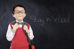 Il bambino porta l'uniforme con il soggiorno del testo a scuola Immagini Stock