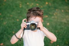 Il bambino prende un'immagine facendo uso della macchina da presa immagini stock