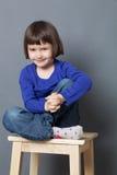 Il bambino prescolare splendido che si siede nella tenuta ha attraversato le gambe Fotografia Stock