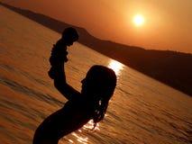 Il bambino, ragazza nel tramonto con il bambino gioca sul mare Fotografie Stock