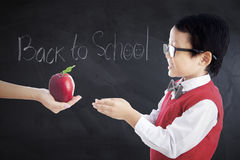 Il bambino riceve la mela con testo di nuovo alla scuola Fotografie Stock Libere da Diritti
