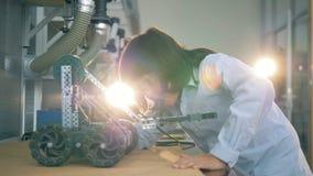 Il bambino salda una costruzione con le ruote, fine su video d archivio
