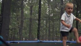 Il bambino salta su un trampolino nel parco stock footage