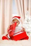 Il bambino Santa tiene un grande contenitore di regalo rosso Immagine Stock