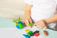 Il bambino scolpisce da plasticine il globo e gli alberi Disposizione del pianeta in palme dei bambini Ecologia di concetto fotografie stock