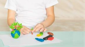 Il bambino scolpisce da plasticine il globo e gli alberi La posizione del pianeta in palme dei bambini Concetto di ecologia immagini stock libere da diritti
