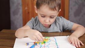 Il bambino sconosciuto disegna con le matite luminose mentre si siede alla tavola Sviluppo e istruzione dei bambini della scuola  stock footage