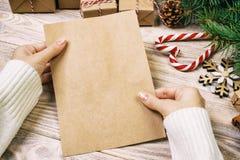 Il bambino scrive le lettere e le tiene in mani su fondo di legno d'annata rustico Formato A4 della lettera del modello immagine stock